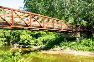 A red, metal bridge over a creek
